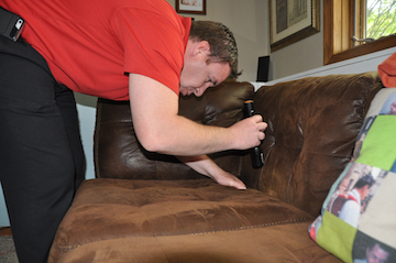 A man uses a flashight to inspect a couch