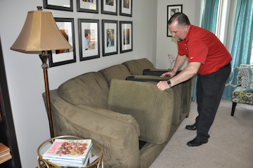 A man inspects a couch cushions for insects