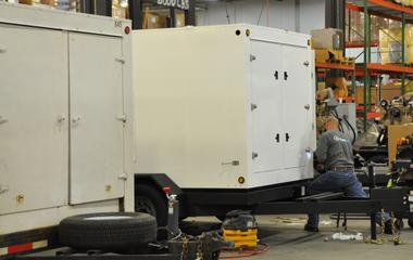 A man moves a couple generators into storage.
