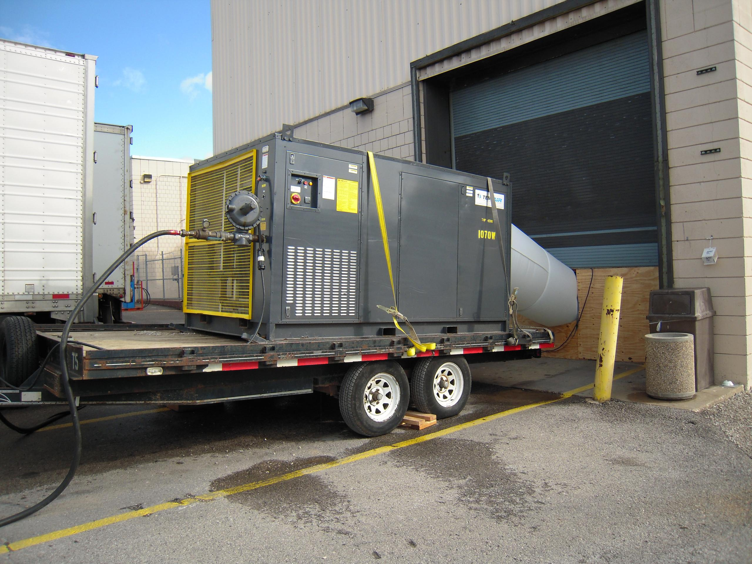 A generator sits ontop of a trailer outside a loading dock